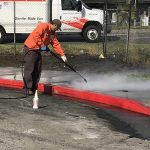 Public Works crew power washing sidewalk covered with oil
